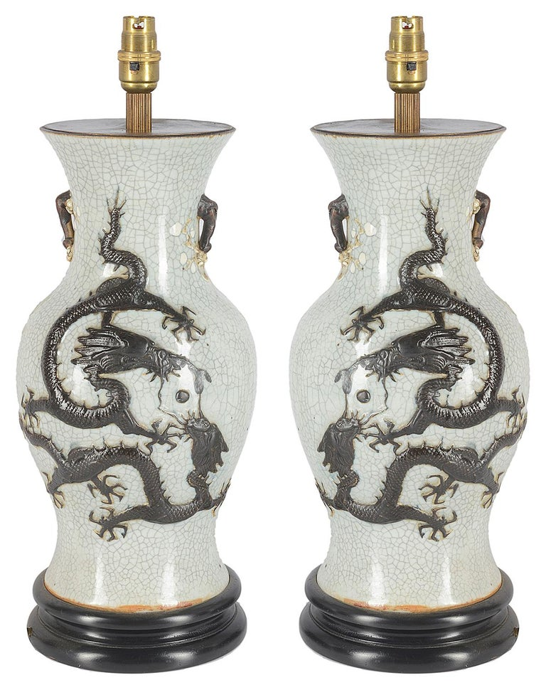 Pair of late 19th century Chinese crackleware vases or lamps. Each having a white ground with a mythical dragon in releaf.