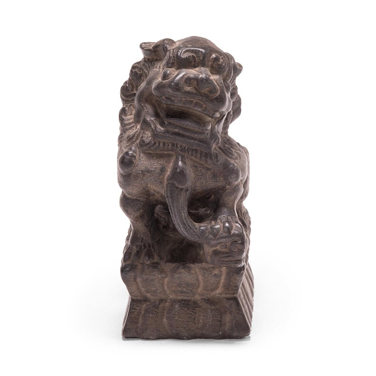 These petite 19th century guardian Fu dogs, each hand carved from a single block of blue stone, once sat upon a family altar table in a grand Provincial Chinese home. The pair represents yin and yang, and they sit in mirrored postures upon lotus