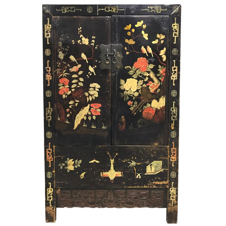 A wonderful pair of 19th century Chinese cabinet with a heavy black lacquer and beautifully painted garden scenes depicting myriad birds including cranes, phoenix, magpies, and ducks amidst a lush landscape of auspicious flowers including peonies,