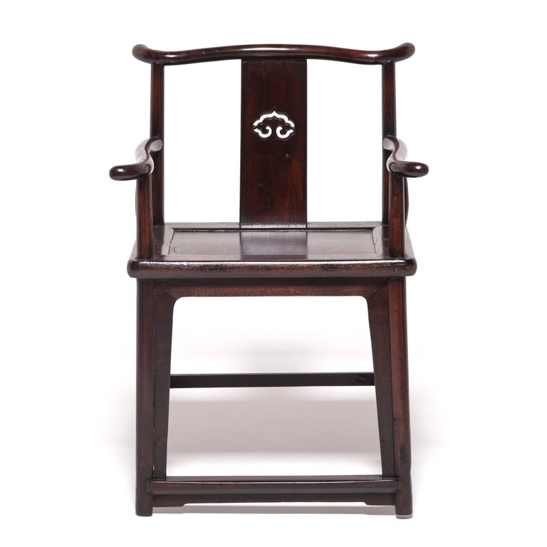 This pair of elegant 19th century elmwood chairs embody Ming-dynasty design with simple form yet complex construction. The walnut chairs are an unusual blend of traditional tall yoke-back design and square low back armchairs, and each bears a ruyi