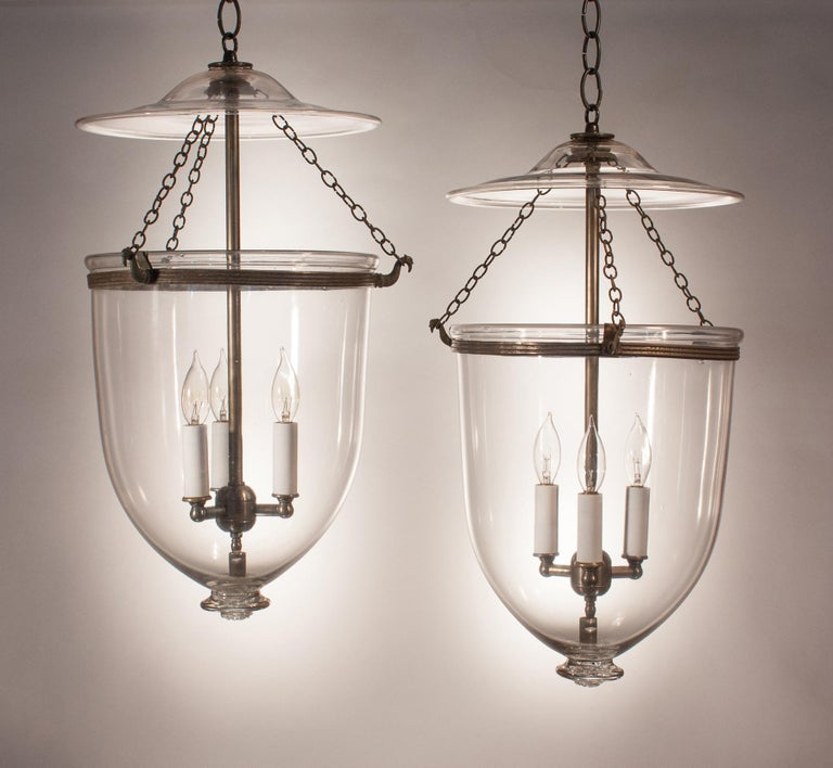 An outstanding pair of bell jar lanterns from England, circa 1870, with original rolled brass bands. The quality of the clear, hand blown glass is excellent, and the glass pontil bases have a nice spiral pattern. The set is very well-matched pair