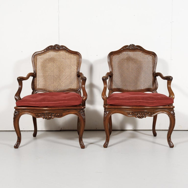 A lovely pair of 19th century Country French Louis XV style armchairs having solid walnut frames and cane seats and backs with removable loose cushions, and raised on elegant cabriole legs, circa 1890s. Each charming provincial armchair features
