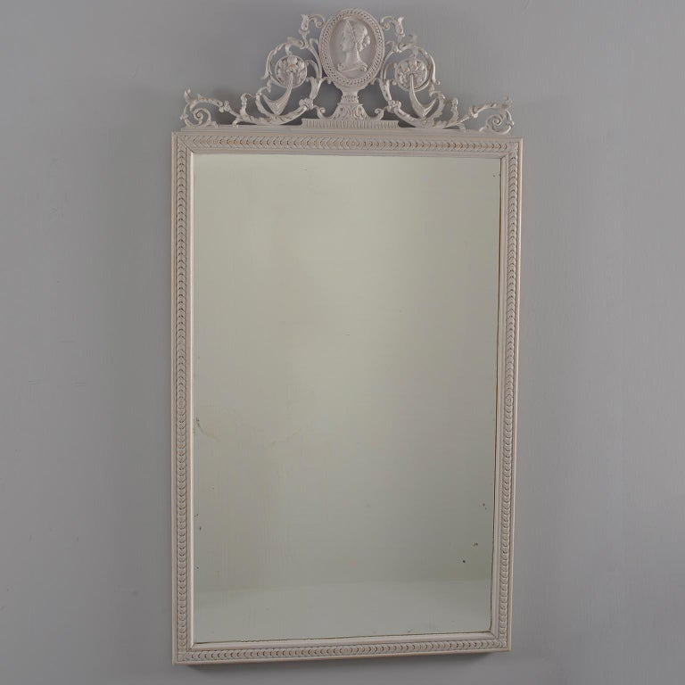 """Pair of Directoire style wood framed mirrors with antique white painted finish feature beveled edges and elaborate crests topped with a carved bust. Sold and priced as a pair, circa 1890.  Actual Mirror Size:  36.75"""" h x 22.75"""" w"""