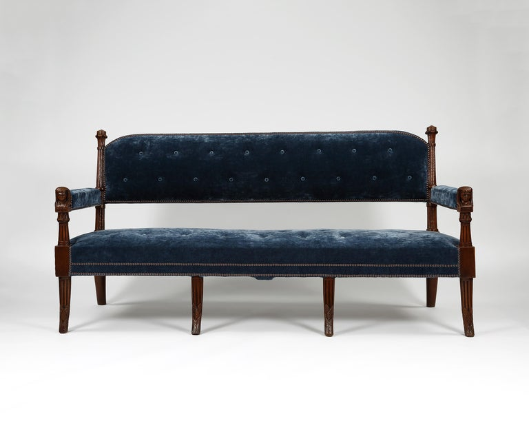 A fine pair of settees in the Egyptian design. The arms are headed with carved Egyptian style heads. Raised on four carved up-rights and upholstered in a velvet by Colefax and Fowler. Similar furniture designs and furnishings can be seen at