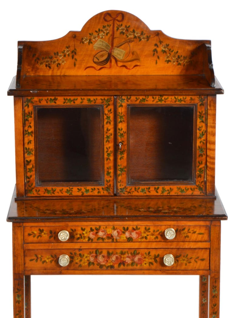 These petite display cabinet stands are uniquely attractive featuring beautiful satinwood painted with flowers, ribbons and classical themes on all three sides. The long tapering legs are joined by a lower shaped shelf and supporting the upper part