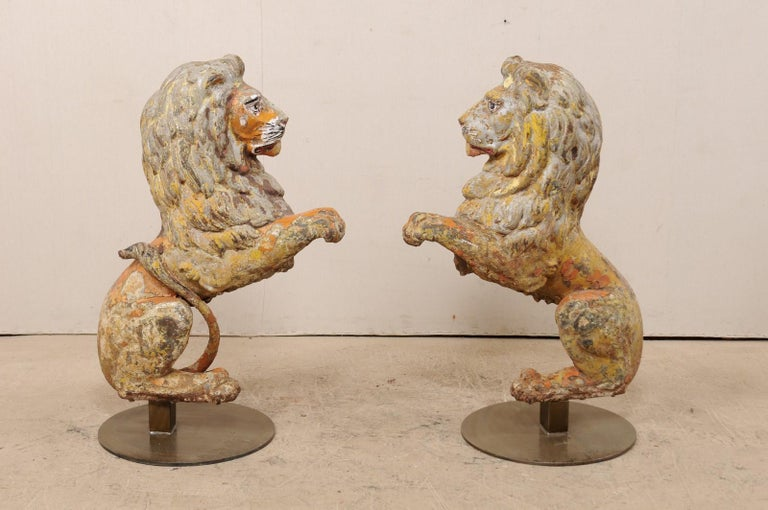 A pair of English lions of cast-iron from the 19th century on stands. This antique pair of cast-iron lions from England are each one half of a pair, with front position being shown at side to create a perfectly seated pair, which have then been