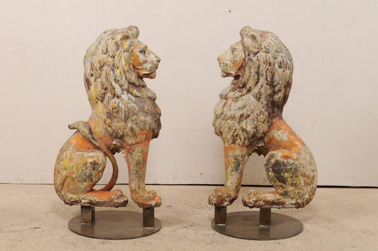 A pair of English sitting lions of cast-iron from the 19th century on stands. This antique pair of cast-iron lions from England are each one half of a pair, with front position being shown at side to create a perfectly seated pair, which have then