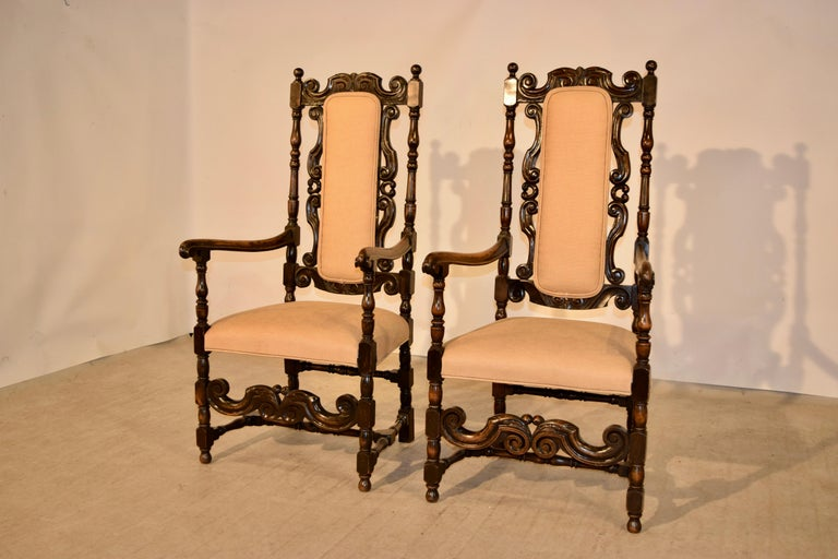 Pair of 19th century oak hall chairs from England. They have wonderfully hand carved backs with hand turned frames. We have had the seats and backs newly upholstered in linen.