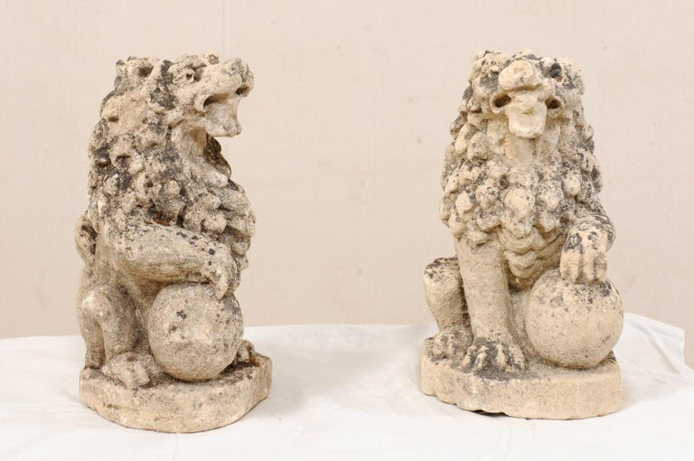 A pair of 19th century English lions from carved limestone. This antique pair of stone lions from England are each shown in seated position with a single front leg or paw raised atop a ball. This pair of lions have gorgeous, full manes of hair and
