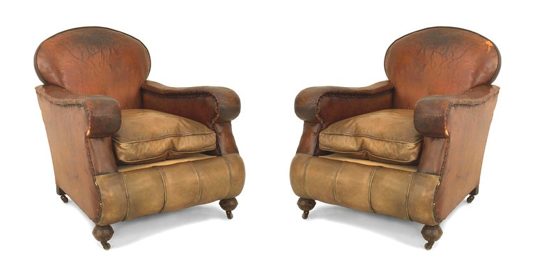 Pair of English Victorian over size brown leather club chairs with a cushion seat and rounded back (condition of leather AS IS).
