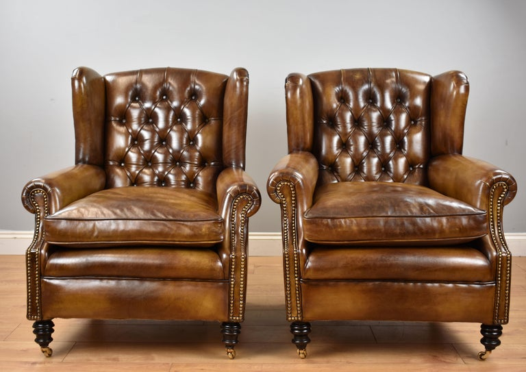 For sale is a good quality pair of Victorian ladies and gents armchairs, each having winged and buttoned backs above a cushion seat flanked by scroll arms, decorated with brass studs. Each chair is raised on turned feet terminating on brass castors.