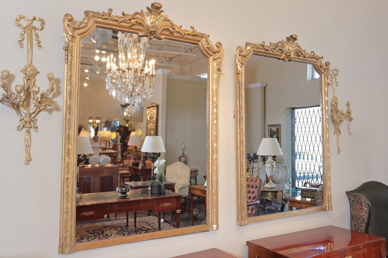 Pair of very fine 19th century French Louis XVI gilt carved large mirrors. Beautiful scroll carving with a center crest design. Partial water gilding still evident throughout. Hand burnished gold in beautiful antique condition exposing some red bole.