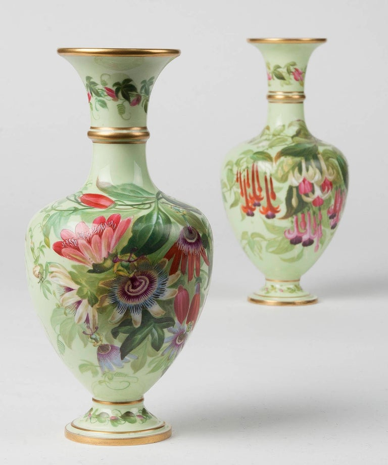 A couple of porcelain vases made by Copeland. The vases were made circa 1860, which can be seen from the used mark on the bottom. The two vases are different, they are painted with various types of flowers, including clematis, fuchsias and