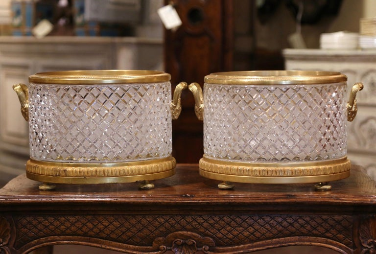 These elegant antique cache pots were created in France circa 1890; round in shape, each Louis XVI style planter rests on a bronze circular base terminating with bun feet. The large jardinières feature a gilt bronze ring around the rim, and are
