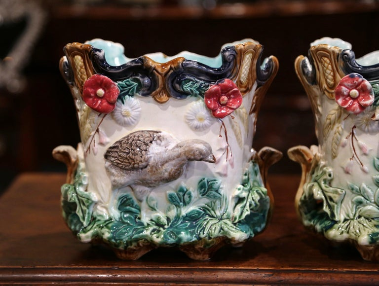 This pair of colorful, hand painted Majolica jardinières was sculpted in France, circa 1870. The antique planters are almost square in shape with scalloped decor around the edges. Each porcelain cachepot features exquisitely rendered hunt and floral