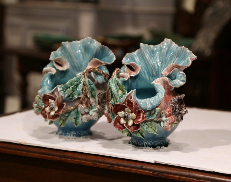 Decorate a console or a buffet with these unusual, antique Majolica vases. Crafted in France circa 1880, each sculptural porcelain cachepot features an asymmetrical, scalloped edge at the pediment. The artful ceramic is heavily decorated with