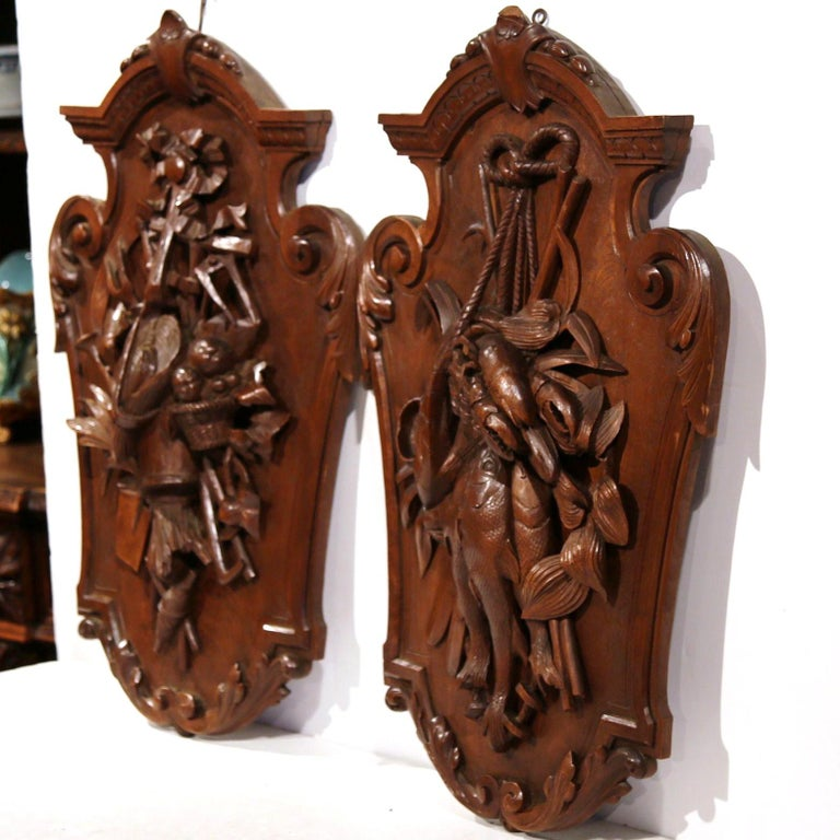 Decorate a ranch or hunting lodge with this pair of antique hand carved wall hanging trophies. Crafted in France, circa 1870, each fruitwood plaque has intricate, detailed carvings depicting two gifts of nature,