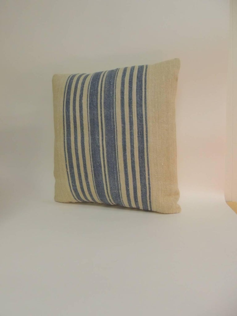 Pair of 19th century French stripes square decorative pillows in Wedgewood blue. The antique textile in the front of these decorative pillows show vertical stripes on tan with a chevron woven homespun textile. French decorative cushions finalized