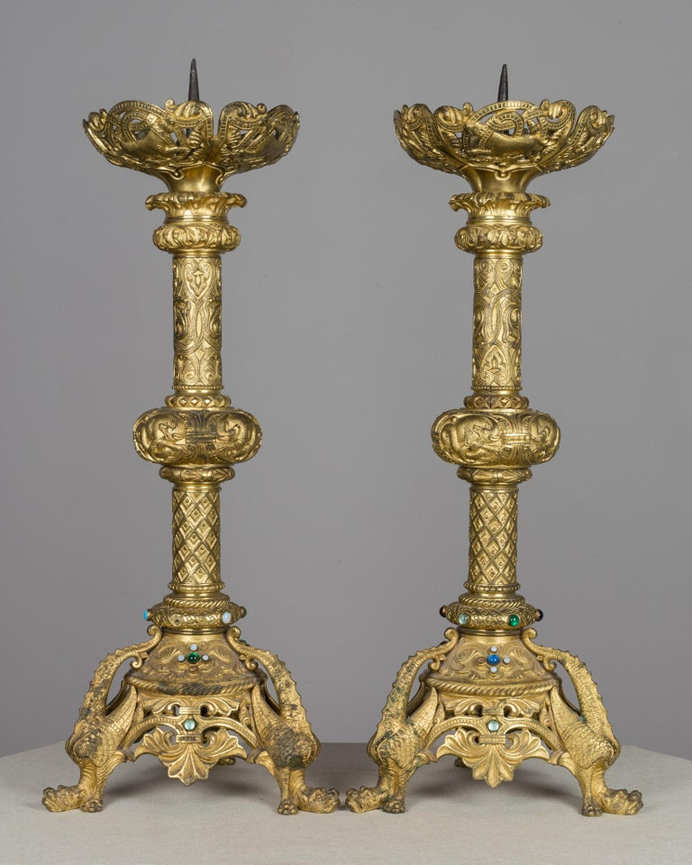A pair of large ornate French bronze doré candlesticks. Heavy cast bronze with pierced decoration and set with colorful cabochon jewels. Triangle base with fantastic winged dragons. Large prickets for pillar candles and deep cups to catch melting