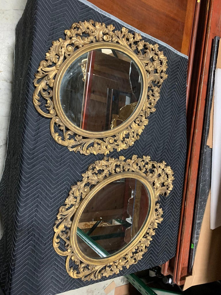 Pair of 19th Century English carved giltwood oval mirrors.