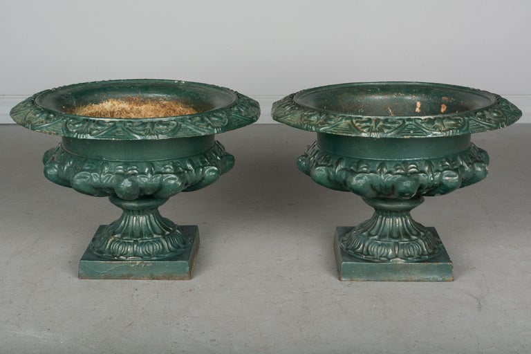 A pair of 19th century French cast iron garden urn planters, with original weathered green painted patina. Weight: 40 lbs. each. 11.5