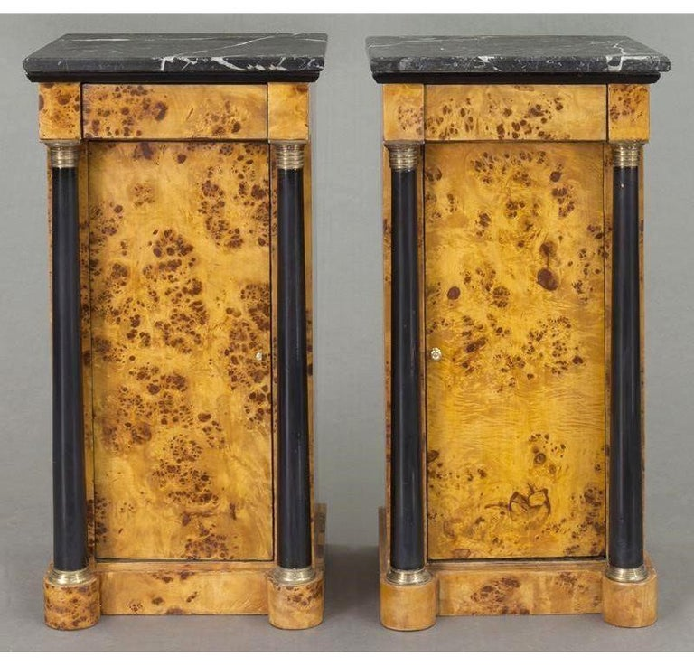 These elegant, antique bedside tables were created in France, circa 1890. Both matching cabinets are made of elm wood; they have a recessed center door flanked by a pair of round, ebonized columnar supports decorated with brass rings both at the