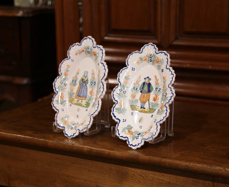 Decorate a kitchen wall or a shelf with this pair of antique decorative plates. Crafted in Brittany circa 1890, each faience plate is hand painted with traditional Breton figure motifs, and is further embellished with floral decor. Both platters are