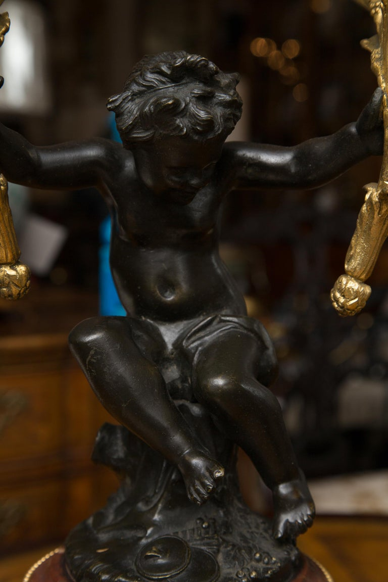 These are impressive pair of 19th century gilt metal candelabra held by an exquisitely patinated bronze cherubs'. They are placed on rouge marble and decorated circular bases decorated also with gilt metal accents. The black plinths add a depth to