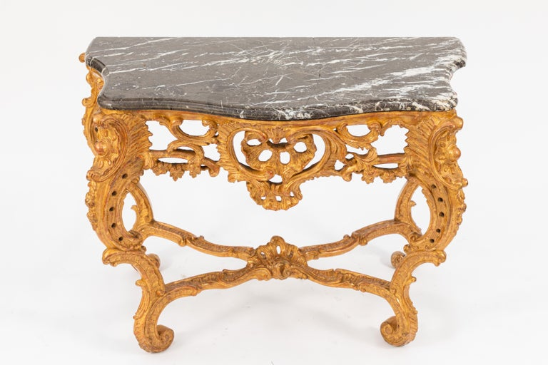 Pair of early 19th century French giltwood consoles with marble tops. The marble tops are believed to be original as the backs are hand chiseled. One marble top has a repair. These consoles were purchased at Christies.