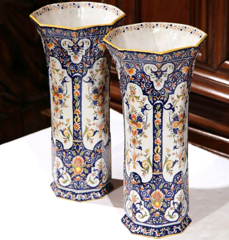 Incorporate beauty and color into your home with this elegant pair of antique ceramic vases, crafted in Rouen, France, circa 1860, the tall colorful vessels feature a circular bottom and a wide mouth at the top with floral motifs. Both vases are in