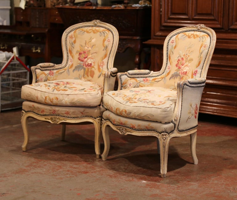 These elegant antique fruitwood bergeres were crafted in France, circa 1860. Both Louis XV style Baroque armchairs have a curved, pitched back. The chairs are decorated on the pediment, curved legs and armrests with hand carved floral