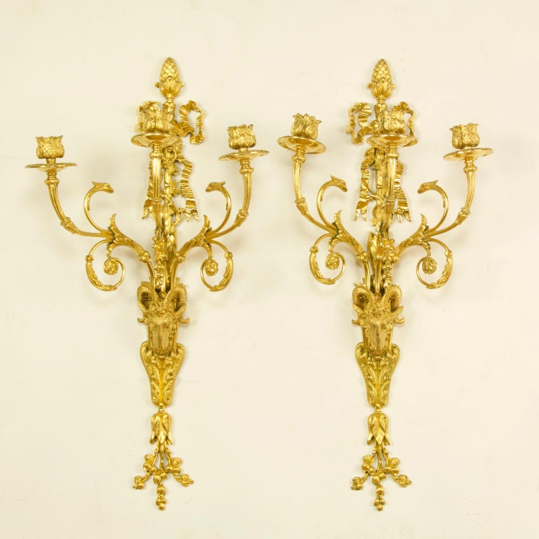 Pair of large French 19th century Louis XVI goat heads three-light wall lights/sconces  A pair Louis XVI style gilt bronze three-branch wall lights, each with a backplate the lower part of which is in the form of a goat's head resting on a foliage
