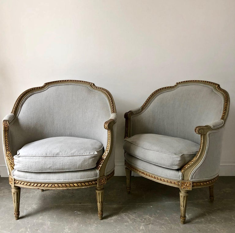 A pair of 19th century French Gondola bergères in Louis XVI style. The frames richly carved the top gracefully curved, the seat rails and the fluted legs with florets.showing some giltwood. Completely re-upholstered in pale blue linen, France, circa