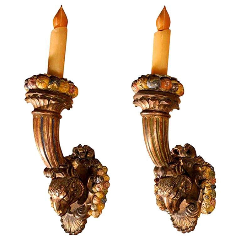 Grand scale and well carved antique French Napoleon III giltwood and polychrome torch sconces with rams heads, and fruit accents. These antique French Louis XVI style carved wood sconces have a gorgeous warm aged patina and are newly wired for the
