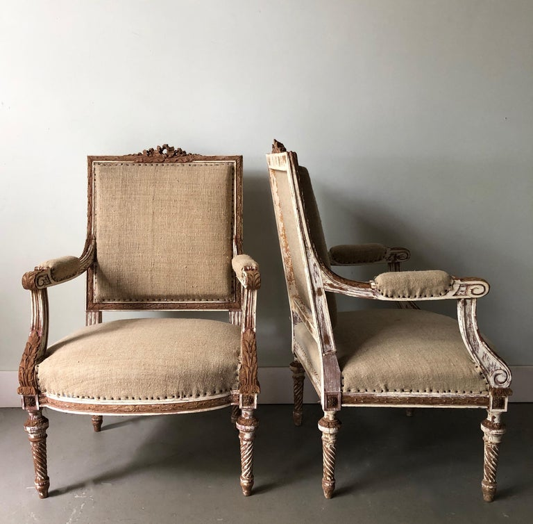 A pair of 19th century French armchairs à la reine with flat back and richly carved solid wood frame with ribbons, acanthus and rosettes on conical twisted fluted legs, showing some places fragments of original giltwood. Upholstered in raw