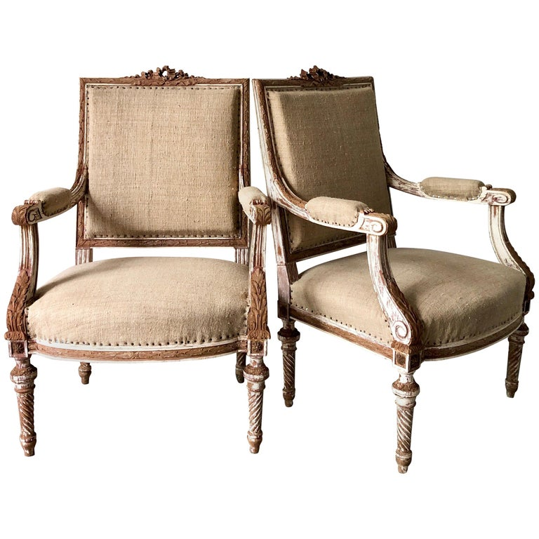 A pair of 19th century French armchairs à la reine with flat back and richly carved solid wood frame with ribbons, acanthus and rosettes on conical twisted fluted legs, showing some places fragments of original giltwood.