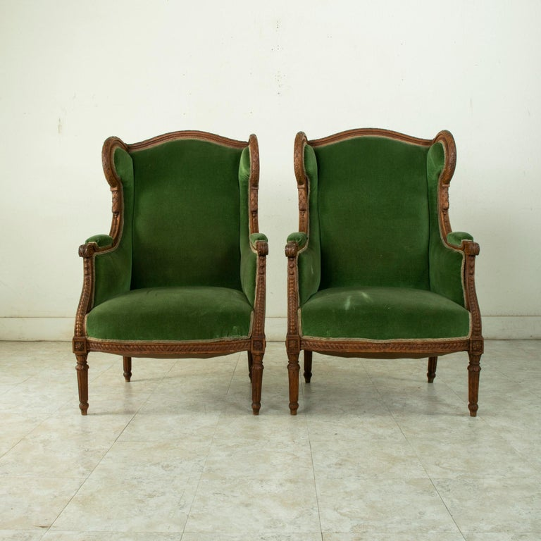 This pair of late nineteenth century French Louis XVI style walnut wingback armchairs or bergeres features hand carved detailing of laurel along the seatbacks, acanthus leaves on the scrolled armrests, and rosettes at the die joints. Additional