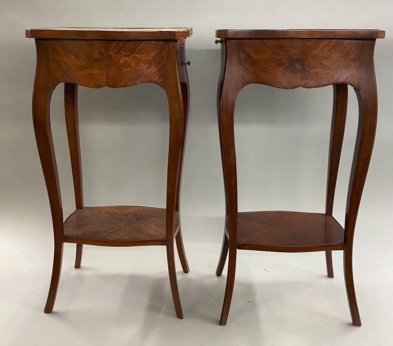 A fine pair of French rosewood end tables with foliate marquetry, each with a shaped top and single conforming drawer, as well as a candle slide on the back with gilt bordered tooled leather, supported by slender cabriole legs and a marquetry single