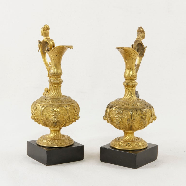 This pair of mid-19th century French Napoleon III period gilt bronze cruets features elegant detailing of leaves and winged female busts on the scrolling handles. A long spout is finished with incised scrolling. Each cruet rests on a 2.25 inch