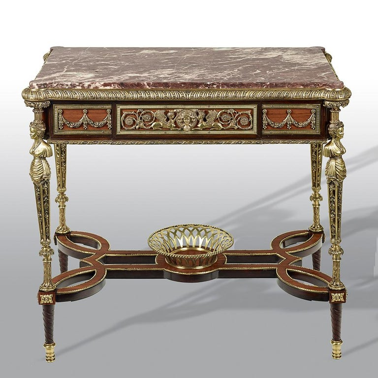 An extremely fine pair of French gilt bronze mounted mahogany table de milieu, in the manner of Adam Weisweiler. The rectangular inset fleur de pecher marble tops above a panelled frieze applied with a pierced scrolling vine mount, with one long