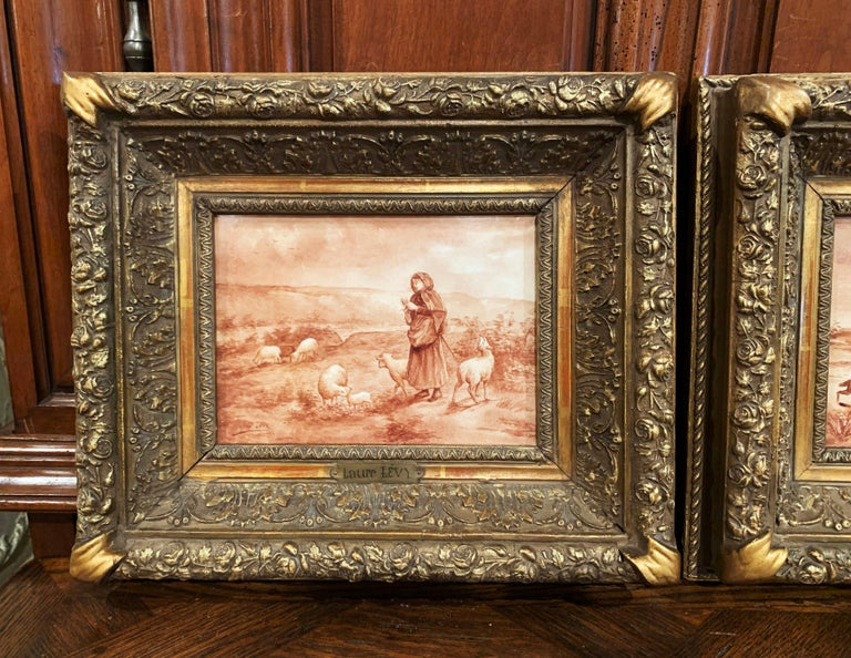 Crafted in France circa 1890, and set in the original carved giltwood frames, both antique porcelain plaques depict a hand painted pastoral scene in the beige and white palette. One painting features a shepherdess attending her sheep, the other