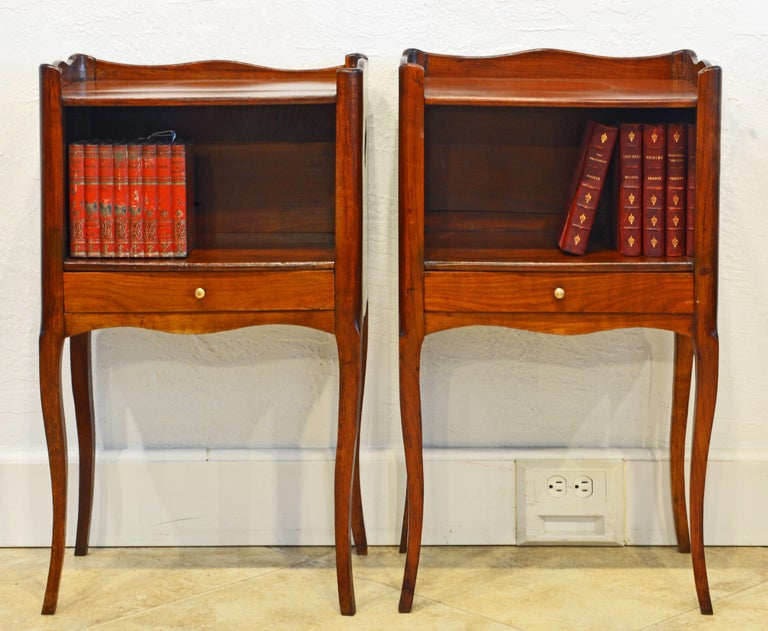 This pair of French Provincial tables or stands feature polished tops surrounded on three sides by scalloped edges above open compartments over drawers and resting on elegant cabriole legs. A charming detail are the clover shape cutouts in both