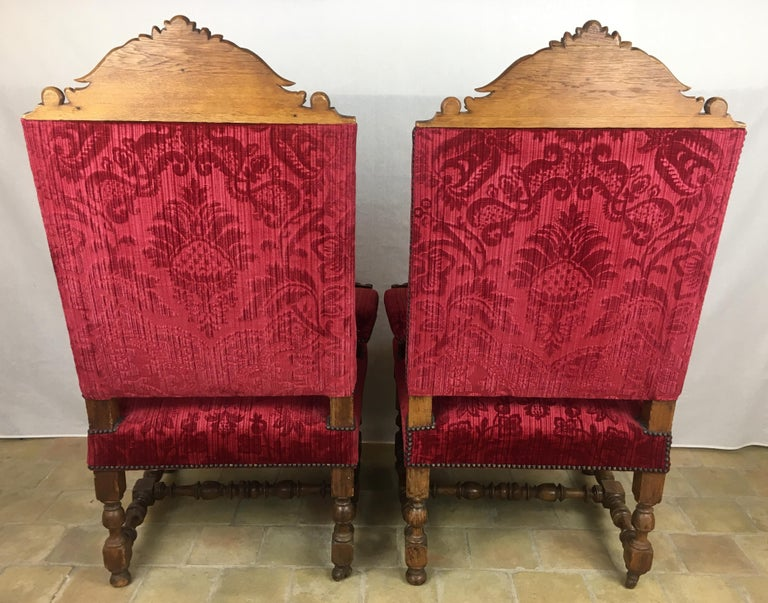 Pair of French 19th century Revival Louis XIII style throne armchairs with hand carved figures on the raised arm rests and top of the chair backs.  These quality throne armchairs feature high slanted backs, the velvet upholstery contrasts nicely