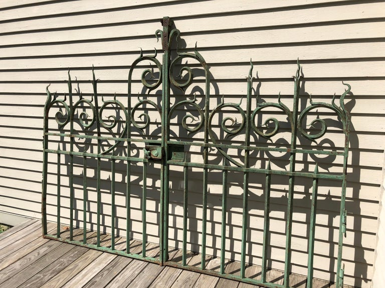 These gates are absolute stunners! All hand-wrought from heavy iron and sourced from a vineyard in Bordeaux, they feature their original green paint with mild surface rusting. Their spectacular detailing and craftsmanship is evident throughout and