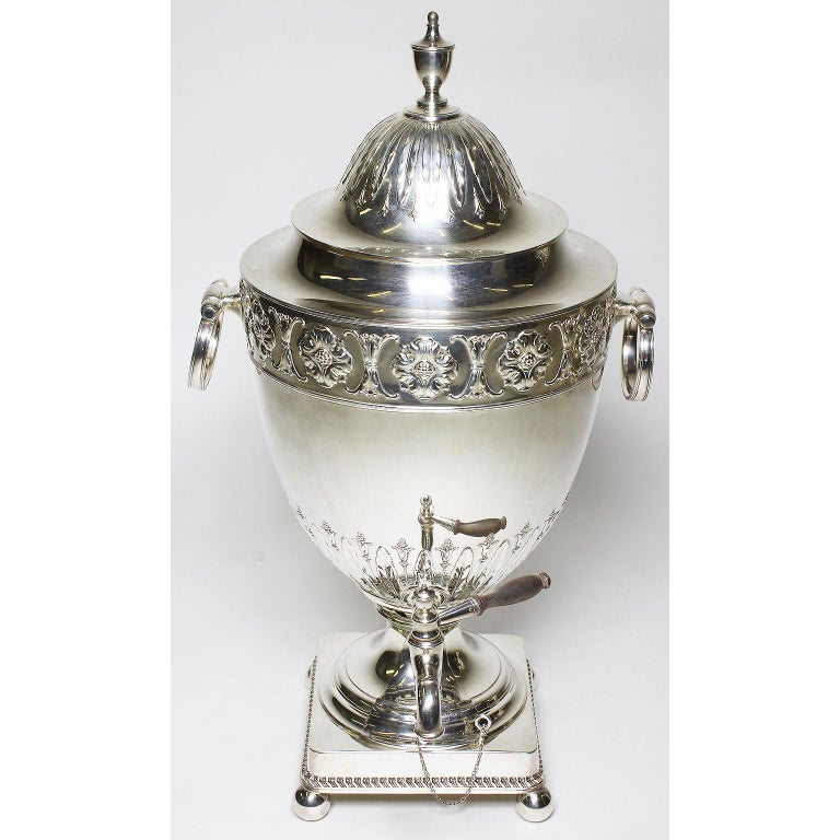 A fine and large pair of English 19th century George III style plated hot water-tea Samovars, each urn-form finely chased with a floral design reservoir with side ring-shaped handles, surmounted by a domed cover and raised on square base and ball