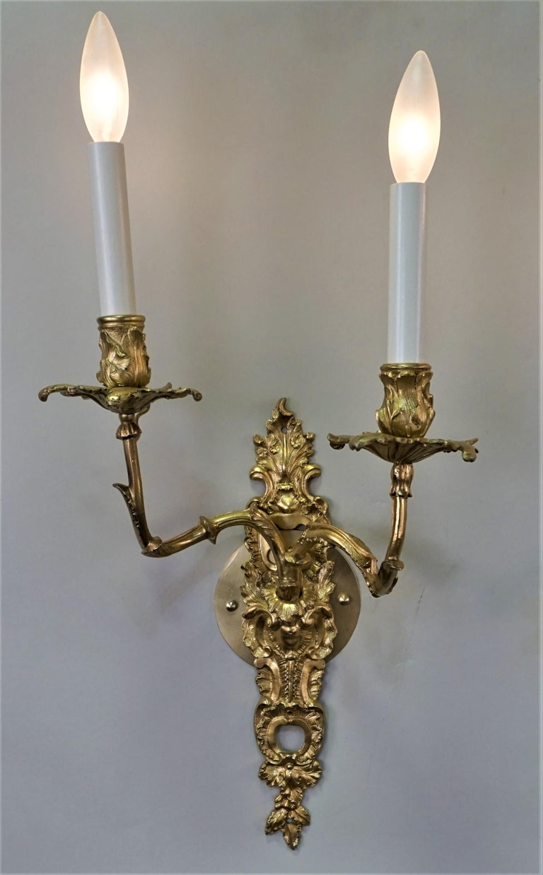 Pair of double arm gild bronze candle wall sconces that have been professionally electrified.
