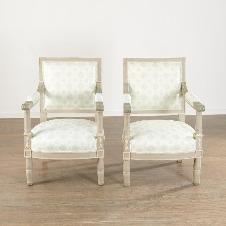 Pair of 19th century Swedish paint decorated armchairs. Each in a nice complimenting upholstery on gray and white painted antique frames. Strong and sturdy are this finely painted antique armchairs. The wide deep seating area making them comfortable