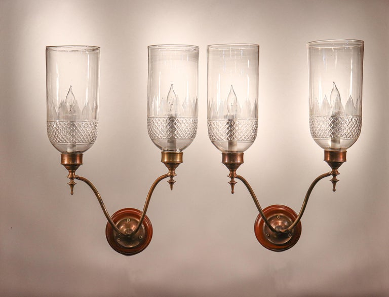 A rare set of four Classic English hurricane sconce shades with cut-glass etching at their bases. The quality of these circa 1900 shades is very good, with several desirable air bubbles in the hand blown glass. The shades arrive ready to install