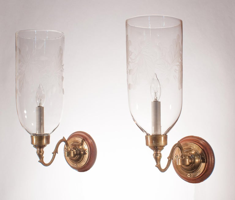 A beautiful pair of late 19th century hurricane shades with straight form and a tasteful frosted leaf motif. The quality of the handblown glass is excellent, with some subtle swirling in the glass. Originally for candles, the wall sconces have been