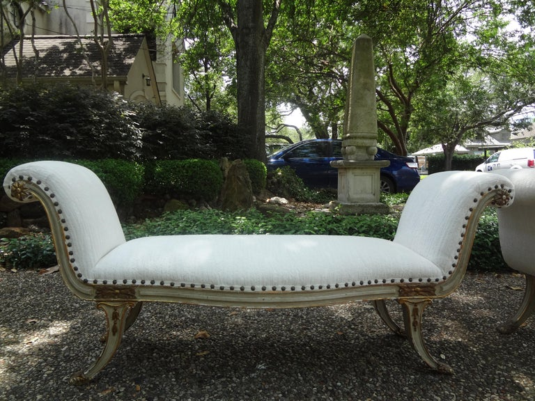 Stunning long pair of 19th century neoclassical style Italian painted and parcel gilt benches. These shapely Italian benches with Klismos style legs are painted cream with gilt trim and newly upholstered in cut velvet with spaced nail head detail.